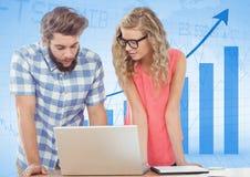 Человек и женщина на компьтер-книжке против голубой диаграммы Стоковое фото RF