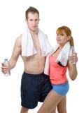 Человек и женщина на спортзале в фитнесе attire держать бутылки с водой Стоковые Изображения RF