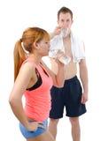 Человек и женщина на спортзале в фитнесе attire держать бутылки с водой Стоковое Изображение RF