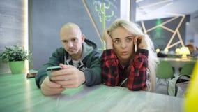 Человек и женщина на таблице в кафе Девушка с светлыми волосами говоря оживленно на телефоне она имела важную видеоматериал