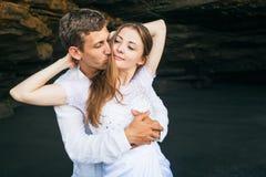 Человек и женщина обнимают с улыбкой на черной предпосылке пляжа Стоковые Фото