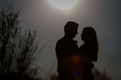 Человек и женщина обнимая на заднем плане заходящего солнца силуэт Стоковые Изображения RF