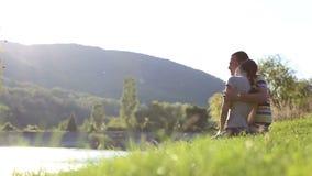Человек и женщина около воды на речном береге. видеоматериал