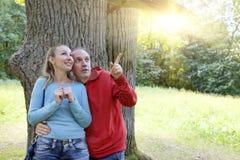 Человек и женщина около дуба в летнем дне видели что-то выше на ветви и смотрят с улыбкой Стоковые Фотографии RF