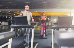 Человек и женщина, пара в спортзале бегут на третбанах стоковая фотография