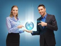 Человек и женщина показывая глобус земли на ладонях Стоковые Изображения RF