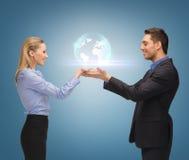 Человек и женщина показывая глобус земли на ладонях Стоковые Фото