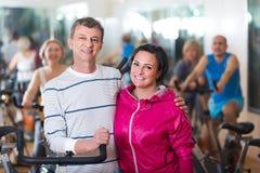 Человек и женщина представляя в спортзале и усмехаться Стоковая Фотография
