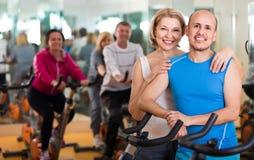 Человек и женщина представляя в спортзале и усмехаться Стоковое Фото