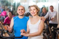 Человек и женщина представляя в спортзале и усмехаться Стоковые Изображения RF