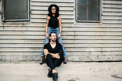 Человек и женщина представляя на стене серого цвета предпосылки Стоковая Фотография