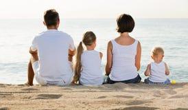 Человек и женщина при дети сидя с назад к камере на пляже Стоковая Фотография RF