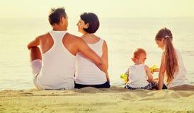 Человек и женщина при дети сидя с назад к камере на пляже Стоковые Изображения
