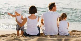 Человек и женщина при дети сидя с назад к камере на пляже Стоковое Фото