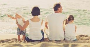 Человек и женщина при дети сидя с назад к камере на пляже Стоковая Фотография