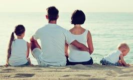 Человек и женщина при дети сидя с назад к камере на пляже Стоковые Фотографии RF