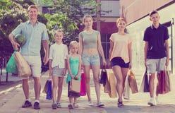 Человек и женщина при 4 дет идя и держа хозяйственные сумки Стоковое Изображение RF