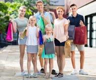 Человек и женщина при 4 дет идя и держа хозяйственные сумки Стоковое фото RF