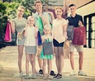 Человек и женщина при 4 дет идя и держа хозяйственные сумки Стоковые Фотографии RF