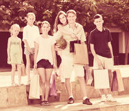 Человек и женщина при 4 дет идя и держа хозяйственные сумки Стоковое Изображение