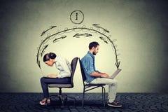 Человек и женщина работая на компьтер-книжках обменивая информацию Стоковое Фото