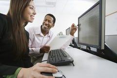 Человек и женщина работая совместно в лаборатории компьютера Стоковые Фото