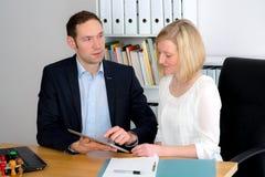 Человек и женщина работая совместно в офисе Стоковая Фотография