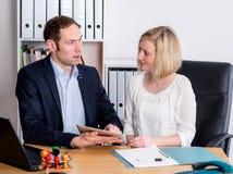 Человек и женщина работая совместно в офисе Стоковые Фото