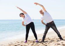 Человек и женщина работая совместно на пляже Стоковые Фото