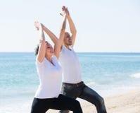 Человек и женщина работая совместно на пляже Стоковое Изображение RF