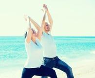 Человек и женщина работая совместно на пляже Стоковое Изображение