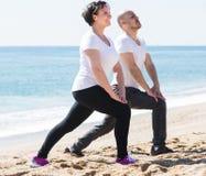 Человек и женщина работая совместно на пляже Стоковое Фото