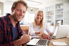 Человек и женщина работая совместно дома Стоковые Фото