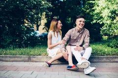Человек и женщина сидя на обочине Стоковые Изображения