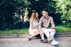Человек и женщина сидя на обочине Стоковое Изображение