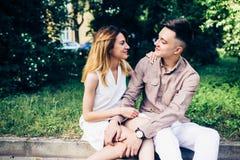 Человек и женщина сидя на обочине Стоковые Изображения RF