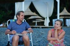 Человек и женщина сидя на пляже Стоковые Фотографии RF