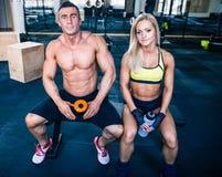 Человек и женщина сидя на стенде на спортзале Стоковое фото RF