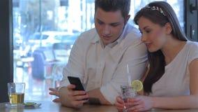 Человек и женщина смотрят smartphone акции видеоматериалы