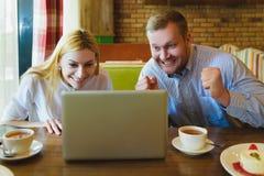 Человек и женщина смотря компьтер-книжку Они счастливы и успешны Стоковое Изображение