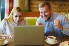 Человек и женщина смотря компьтер-книжку Они счастливы и успешны Стоковое Фото