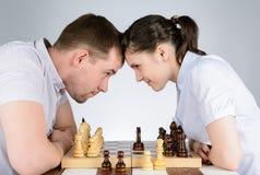 Человек и женщина смотря один другого играя шахмат стоковые фото