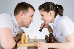 Человек и женщина смотря один другого играя шахмат Стоковое Фото