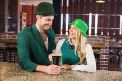 Человек и женщина смотря один другого пока держащ пив Стоковые Фото