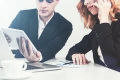 Человек и женщина смотря таблетку Стоковая Фотография RF