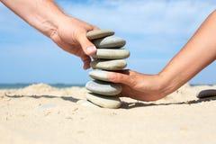 Человек и женщина совместно для того чтобы построить башню сделанную камней Стоковое Фото