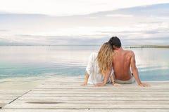 Человек и женщина соединяют сидеть на моле под голубым облачным небом Стоковые Изображения RF