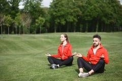 Человек и женщина спорта размышляя в парке Стоковое Изображение RF