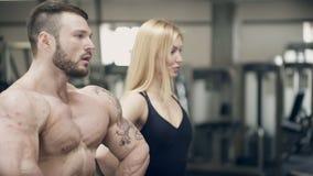 Человек и женщина спортсмена представляя стоять в спортзале сток-видео