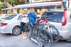 Человек и женщина стоят около 2 велосипедов установленных на хоботе  Стоковое фото RF